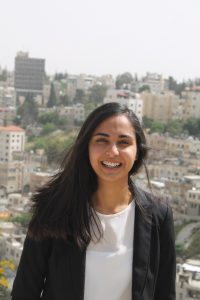 Zina smiling with a city skyline in the background.