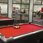 A red pool table with pool sticks leaning against it.
