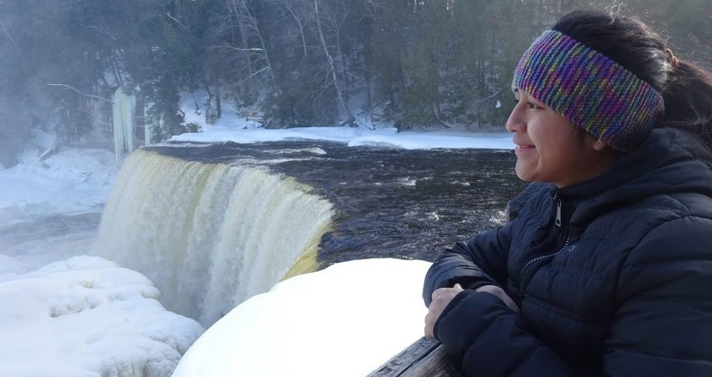 Cecilia stands next to an icy waterfall watching the snow
