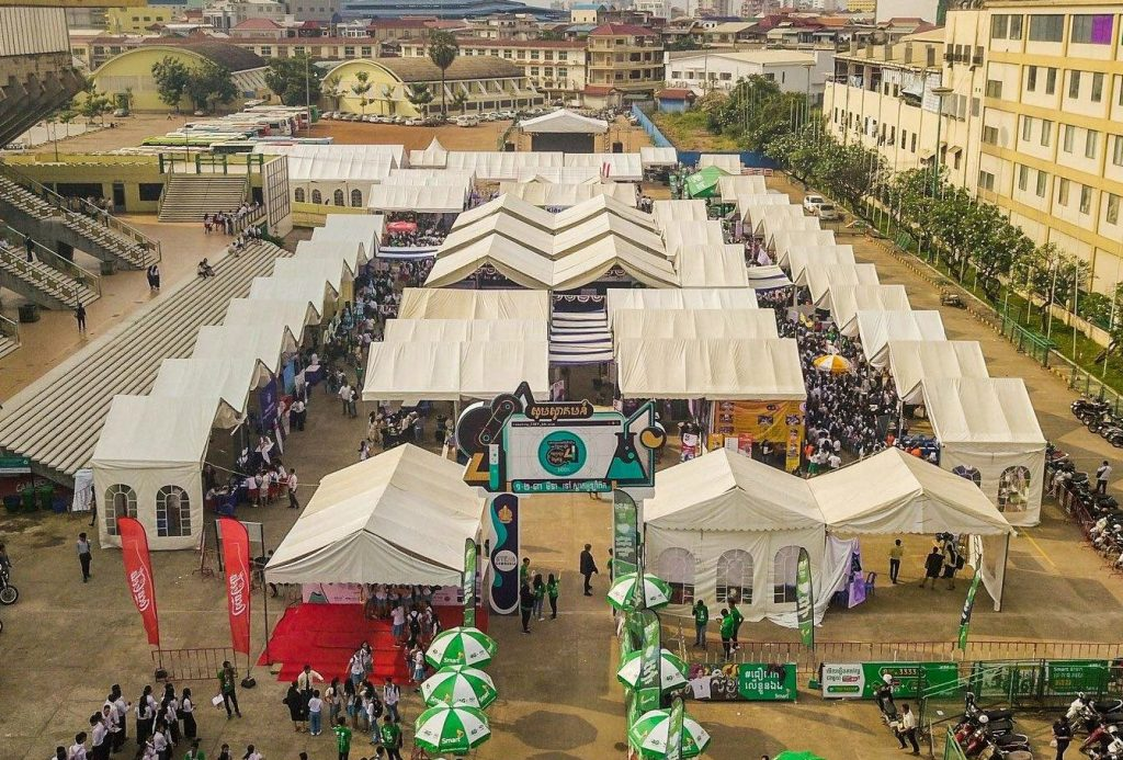 The STEM Festival viewed from above- many white tents, lots of people, and colorful umberellas