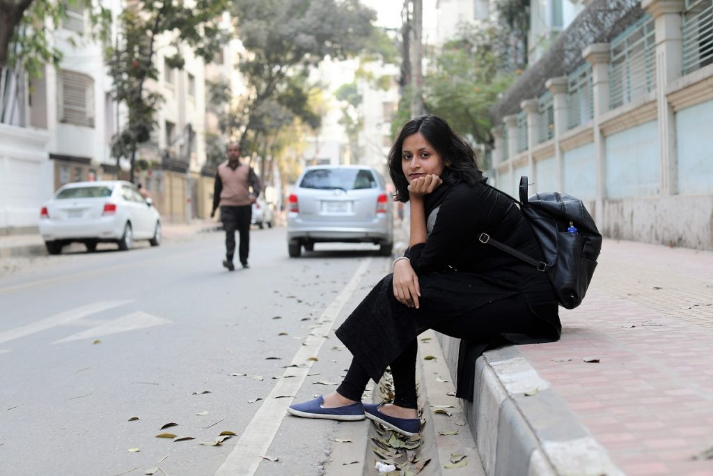 The portrait that Brandon took of Nalifa. Nalifa sits on the sidewalk with her feet in the gutter on a quiet street in Dhaka