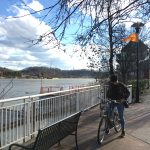 Becky is sitting on her bicycle under a tree by the Tennessee River.