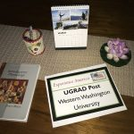 Vicky's UGRAD Post on a table with a succulent, calendar, and notebook