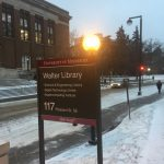 """A standing outdoor post with the words """"Walter Library"""" written on it."""