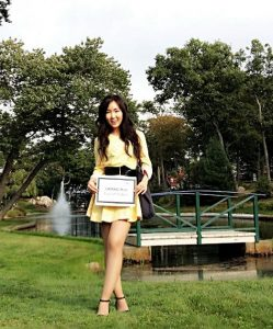 Chessy stands with her UGRAD post in front of a bridge and fountain on campus