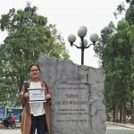 Ngoc holds her UGRAD Post by her home university sign, an engraved stone