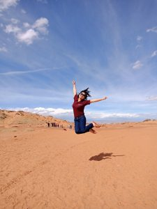 Huong jumps with the blue sky above her and sandstone below her