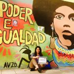 "Johanny sits under a mural of a colorful woman with the words ""Poder E Igualdad"""