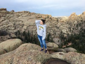 Kseniia looks off into the distance at Vedauwoo standing atop some rocks