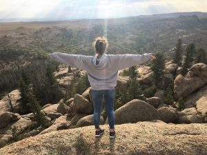 Kseniia put her arms out to welcome the sun from atop the rocky Vedauwoo
