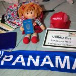 Lourdes' UGRAD Post on her bed with her Panama scarf, hat, schoolbag, doll, and passport
