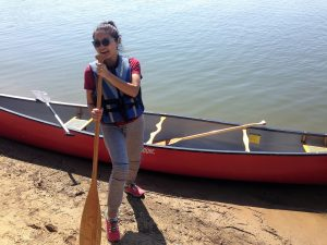 Migma poses with the paddle next to a canoe