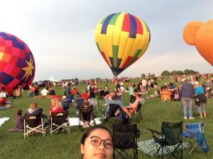 Migma takes a selfie as a hot air balloon lifts off behind her