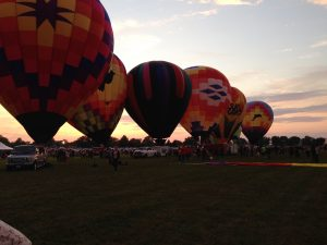 Hot air balloons lined up against the sunset