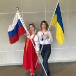 Elizaveta is pictured with another Global UGRAD participant from Ukraine, Helen. They are both holding their country flags.