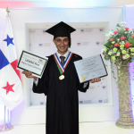 Karan in his graduation gown wearing medals and holding his diploma and UGRAD Post