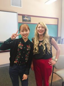 Ni Mo is posing with her English Composition professor, Kelly Lucero in a classroom.